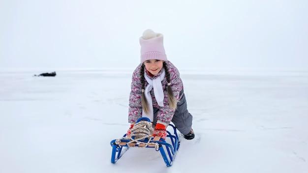 凍った湖、冬、沈黙と野生の自然、ライフスタイルでそりに乗るのを楽しんでいる女の子