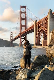 해변에서 골든 게이트 브릿지의 아름다운 경치를 즐기는 여자