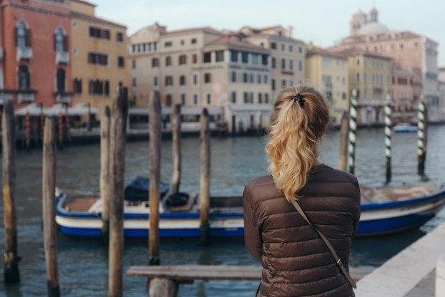 Girl enjoying canal view with boat passing by in venice, italy.