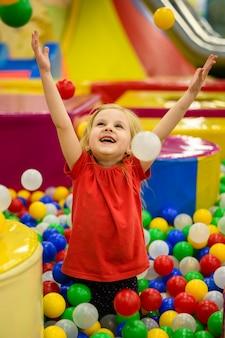 Girl enjoying colorful ball pit