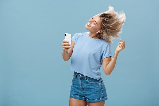 Девушка наслаждается интересными вещами в новых беспроводных наушниках, рекламируя наушники в собственном блоге, записывая видео через смартфон, танцует от радости и восторга, улыбаясь, слушая музыку через синюю стену