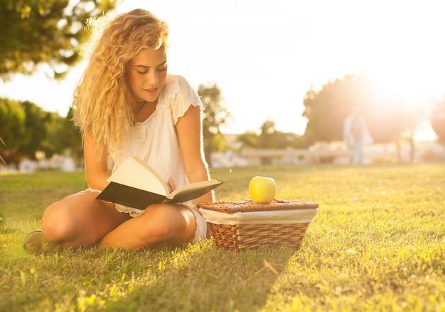 Девочка, наслаждаясь ее книги на открытом воздухе