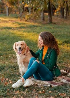 秋の間に外の彼女のペットのゴールデンレトリバーと屋外を楽しんでいる女の子