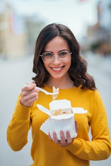Girl enjoying take-away food in the city street, front view.