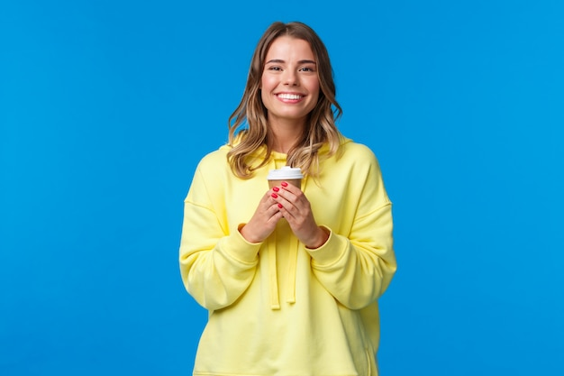 Girl enjoying tasty cup of morning coffee from favorite cafe. cheerful lovely blond woman in yellow hoodie smiling white teeth and holding paper cup of take-away tea, stand on a blue wall