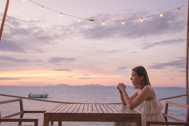 夏休みにトロピカルビューを楽しむ女の子。女性が誰かを待っています。