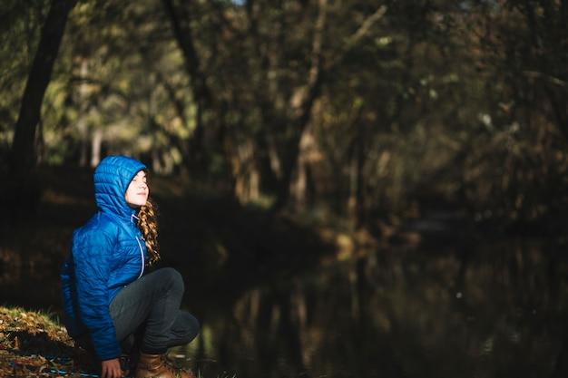 池の近くの天気を楽しむ少女