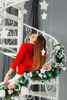 Девушка наслаждается зимой и рождеством на белой лестнице