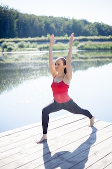 Девочка, наслаждаясь класс йоги на открытом воздухе