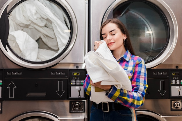 Girl enjoys clean and smelling towels after washing in launderette