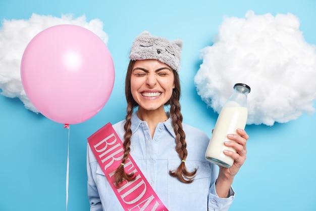 소녀는 축제 행사를 즐긴다 grins 쇼 하얀 치아가 파란색에 고립 된 국내 옷을 입고 신선한 우유를 마실 분홍색 팽창 된 풍선을 보유하고 있습니다.