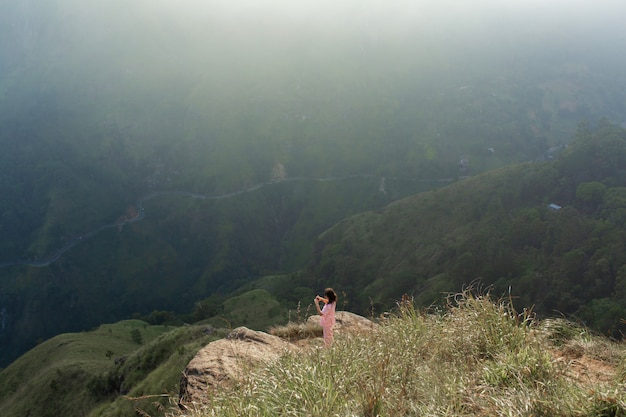 Girl enjoys a mountain view while standing on a cliff