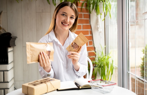 カフェに座っている女の子の起業家は、カメラのカメラにビーガンのための製品食品を見せます。笑顔の中小企業の所有者のブログ。オンラインストアの広告マネージャー。仕事のコンセプト。