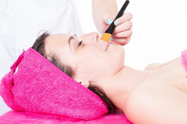 Girl esthetician applying beauty cream on woman face