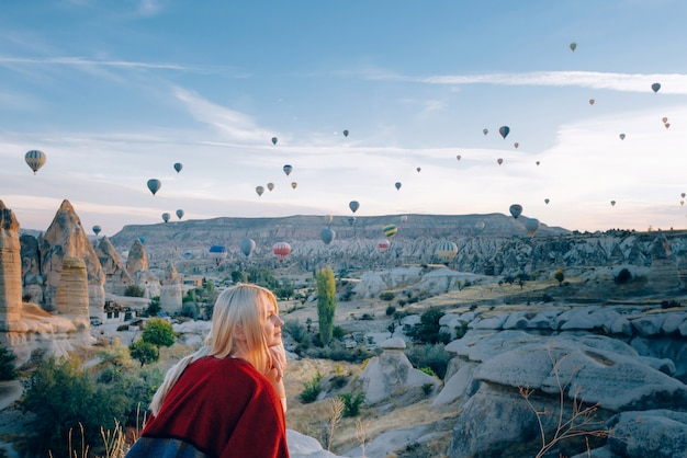 Girl in ethnic clothes at dawn watching the flight a lot of balloons fly over the valley of love