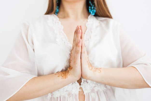 Girl of european appearance, henna drawing on hands, mahendi, girl in light clothes, yoga, spiritual development