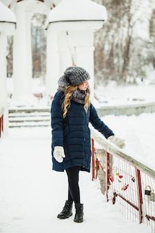 A girl of european appearance walks in the park or forest in winter