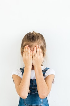 A girl of european appearance with long blond hair covers her face with her hands, fear, play, question, children's emotions