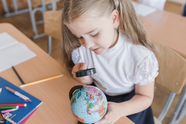 Girl examining globe with magnifying glass
