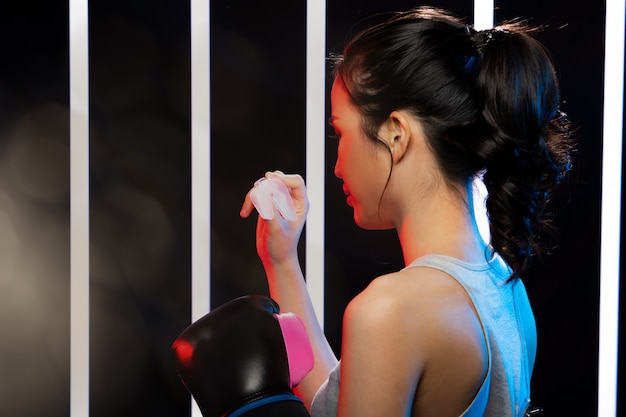 Girl exercises in modern neon boxing gym heavily