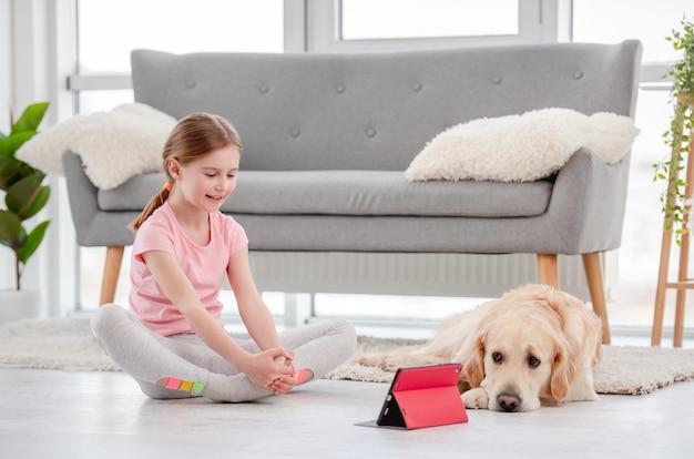犬とオンラインで運動している女の子