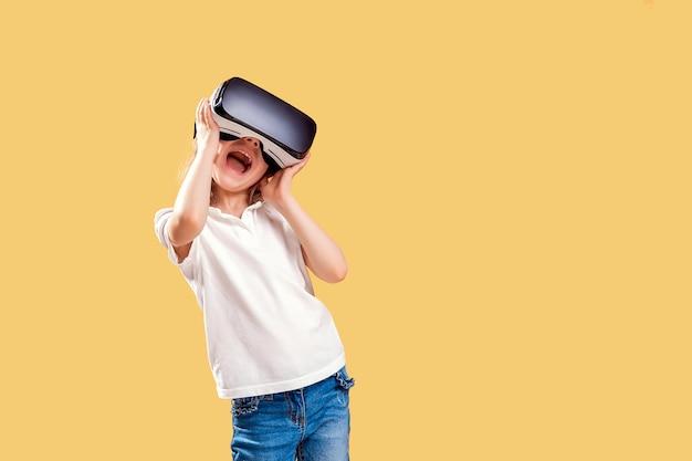 黄色のvrヘッドセットゲームを経験している女の子。彼女の顔に驚いた感情。仮想現実のためにゲームガジェットを使用している子供。