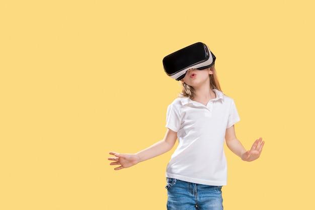 Vrヘッドセットゲームを経験している女の子。彼女の顔に驚いた感情。仮想現実のためにゲームガジェットを使用している子供。