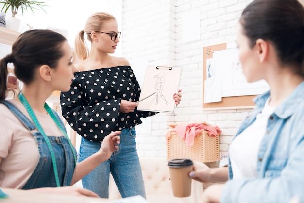 Girl explains to the designer what dress she needs.