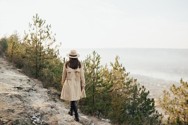 소녀는 언덕을 탐험합니다. 마을, 소나무 숲과 산.