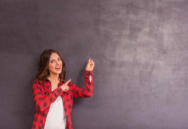 Girl expressing their emotions on gray background for copyspace