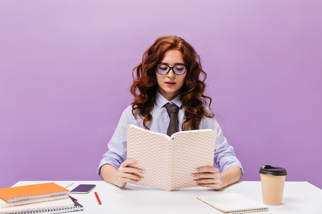 Girl in eyeglasses reads book on purple wall