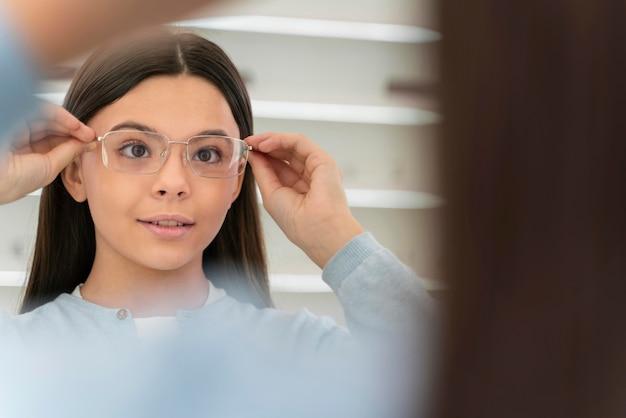 Ragazza in negozio di occhiali cercando su occhiali