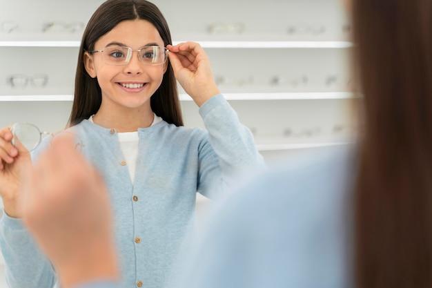 Girl in eyeglasses store trying on glasses