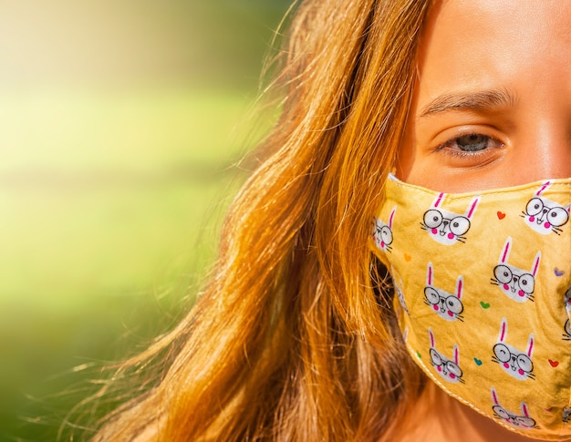Girl in the face mask walks in the park during the day.