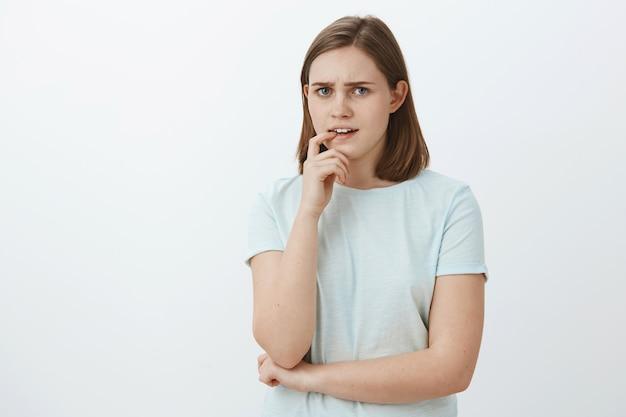 Девушка сталкивается с трудным решением, обдумывает и нерешительно кусает палец, одновременно нахмурившись, выглядит напряженно и озадаченно, имея в виду проблемы и отсутствие плана, обеспокоенно позирует у серой стены