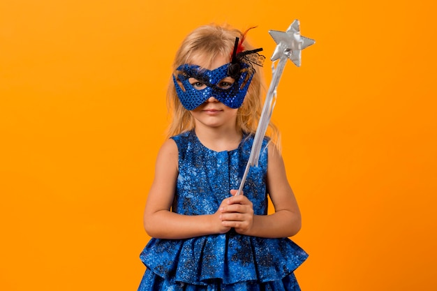 Girl in fairy costume with mask and wand