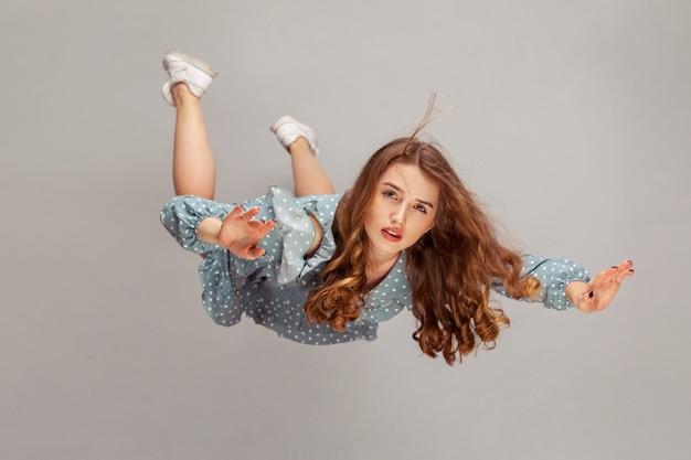 Девушка падает, ее волосы спутаны, взлетая от ветра, модель летит в воздухе