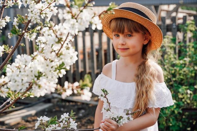 정원에 있는 모자를 쓴 소녀 농부는 꽃이 만발한 정원에서 봄 꽃을 피우는 원예에 종사하고 있습니다