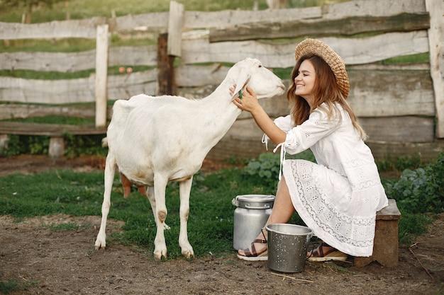 白ヤギの少女農夫。女性と小さなヤギの緑の草。エコファーム。農場と農業の概念。村の動物。