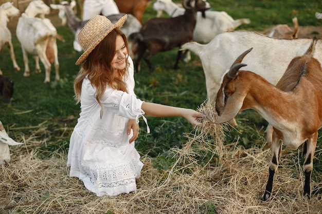 Girl farmer with white goat. woman and small goat green grass. eco farm. farm and farming concept. village animals. girl play cute goat. f