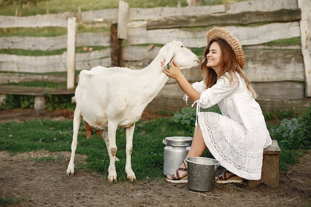 Girl farmer with white goat. woman and small goat green grass. eco farm. farm and farming concept. village animals.