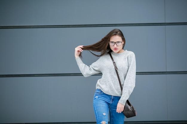 路上でカジュアルな服装の女の子のファッションモデルがカメラを見て、彼女の髪に触れる