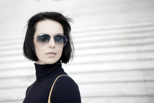 Girl in fashionable glasses outdoor. beauty and urban fashion. look and city style. fashion model pose on stairs background. business woman with stylish short brunette hair, copy space