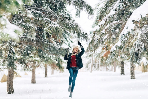 Girl in a fashionable winter hat with a leopard print rejoices in the snow