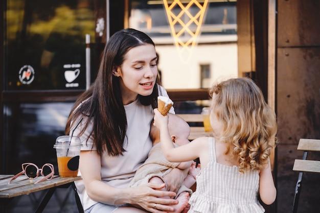 アイスクリームコーンで弟の男の子に餌をやる女の子