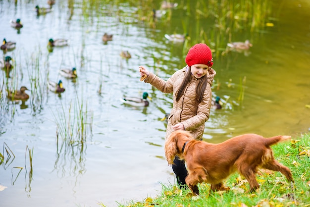 Girl feeding ducks and playing with a dog