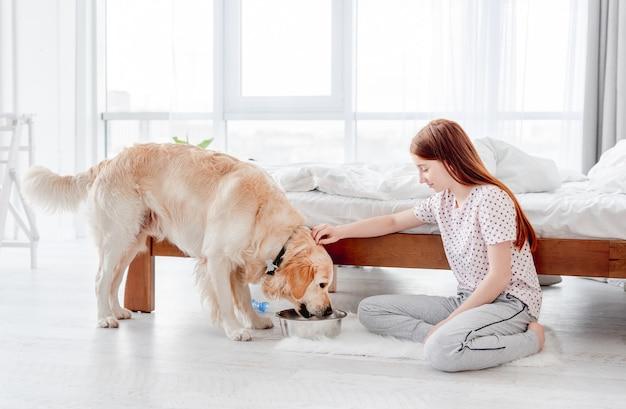 Girl feeding golden retriever dog
