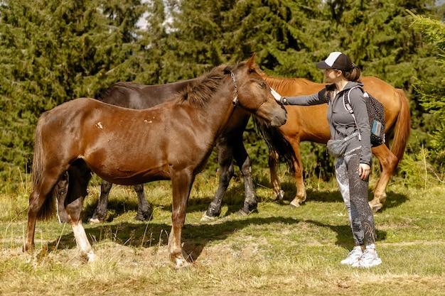 Girl feeding a horse hay in summer. girl feeding horses in the forest
