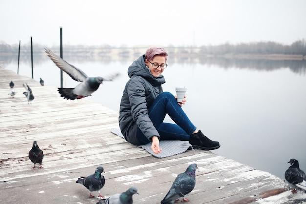 Девушка кормит голубей у озера