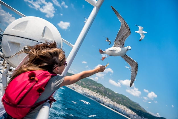 Girl feeding seagulls on the ferry boat
